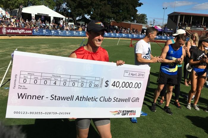 A young man holds an oversized winner's cheque at the Stawell Gift running race in Western Victoria.