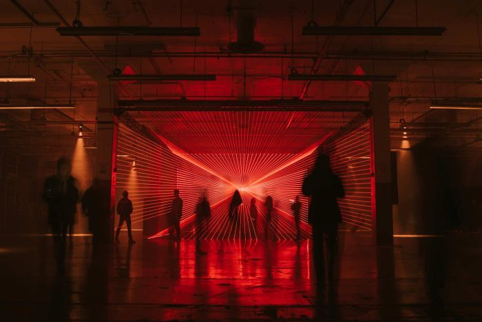 An art installation at Dark Mofo shows many red lasers shooting in a pattern as people walk through it.