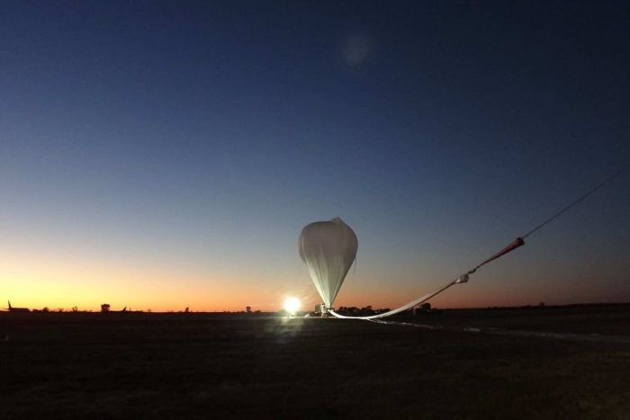 A helium balloon prepares to launch at sunrise in Alice Springs.