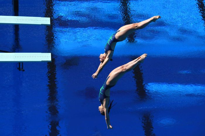 Georgia Sheehan and Esther Qin diving into the water at the Gold Coast Aquatic Centre.
