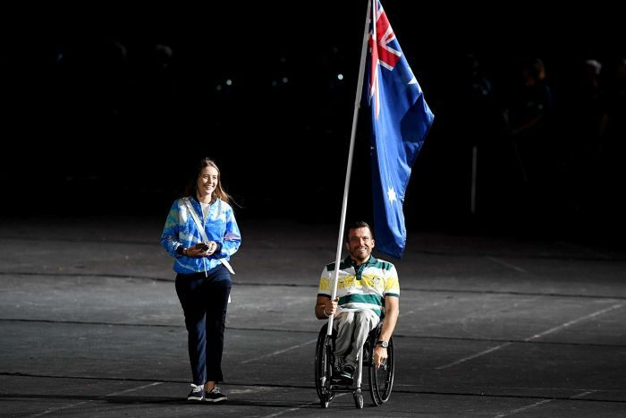 Flagbearer Kurt Fearnley enters the stadium before the start of the closing ceremony of the XXI Commonwealth Games