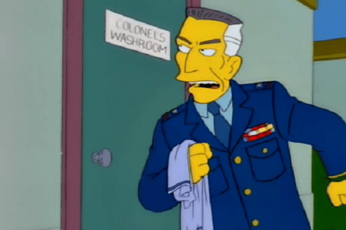 Still from The Simpsons showing a man in a military uniform with a stern expression outside a door that says Colonel's Washroom