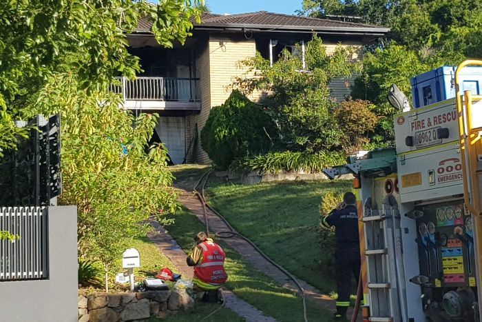Firefighters outside an Everton Hills home in which three people died when a fire broke out.