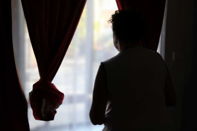 A woman in shadow looking out a window.