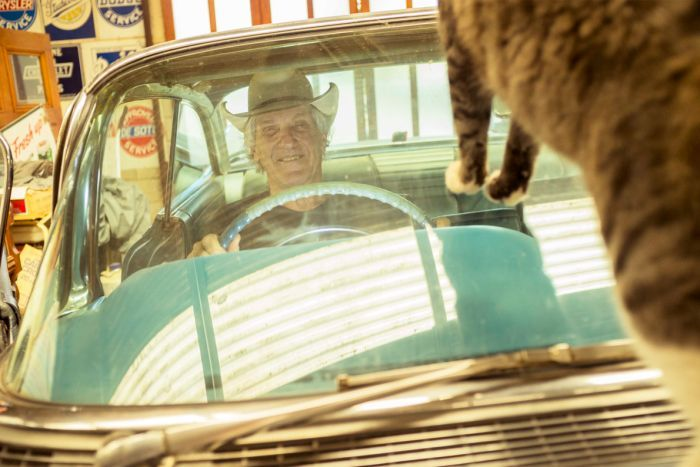 Car collector and magazine publisher Eddie Ford of Newstead sitting behind the wheel of his car with a cat on the windscreen.