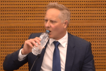 Financial planner Sam Henderson drinks water at the banking royal commission.