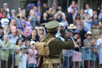 A person dressed as a soldier from World War 1 salutes the Shrine of Remembrance in the Brisbane Anzac Day march.