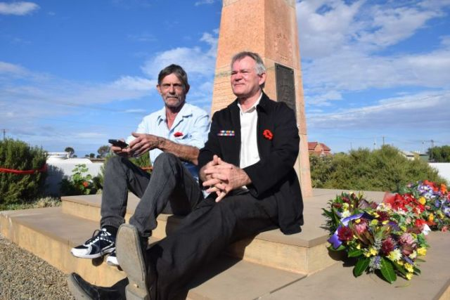 Two men sit on a the base of a war memorial.