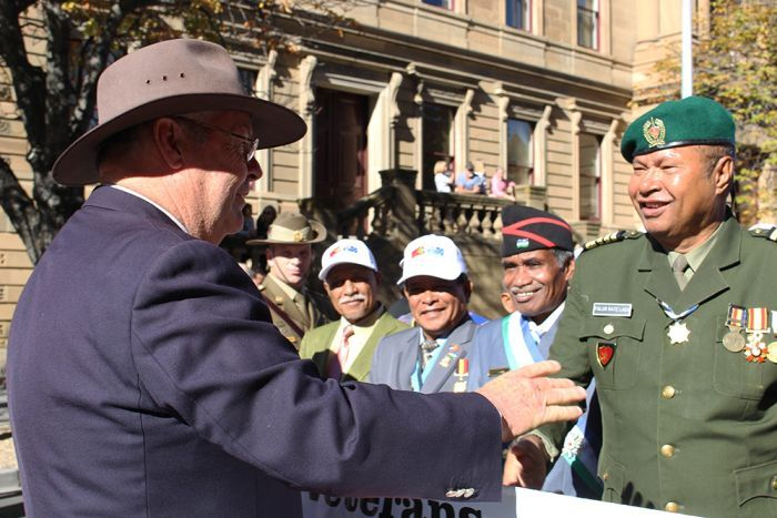 An Australian veteran shakes the hand of East Timorese soldier