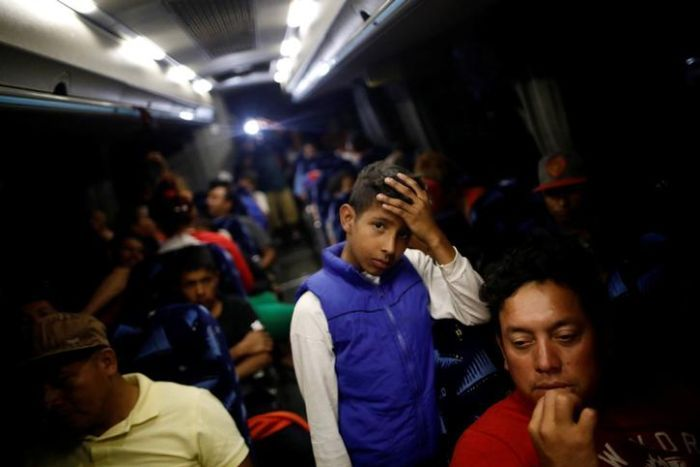 Young migrant rests his head on his hand while standing on a packed bus