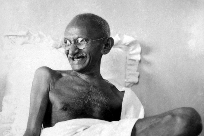 Mahatma Ghandi sits on a bed laughing.