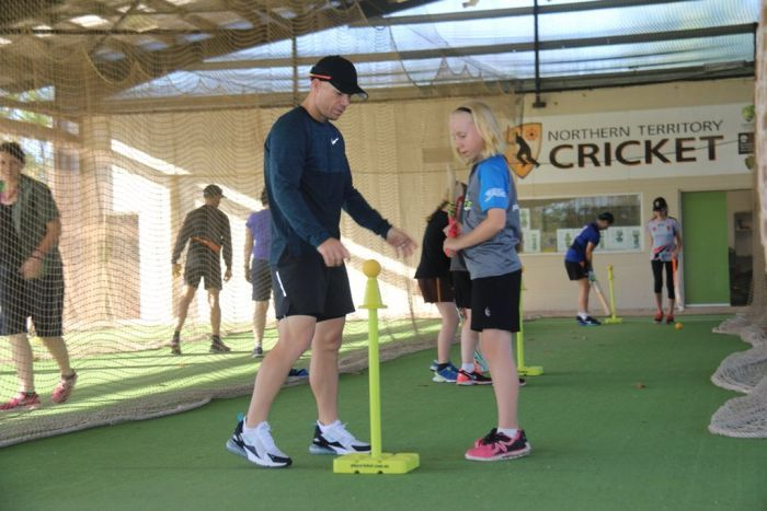 David Warner shows a girl how to play cricket in Darwin.