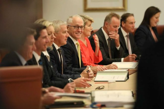 Turnbull is looking towards camera smiling, while his colleagues either side of him are not looking towards camera.
