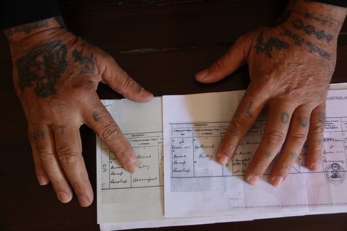 Tattooed hands show the difference between the original birth certificate with the label Aboriginal and the redacted version.