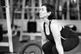A woman in a black tank top lifting a heavy weight in a gym.