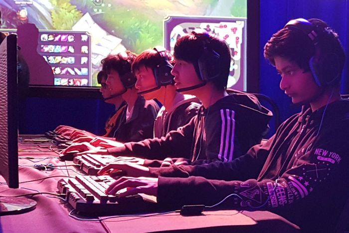 Students sitting in front of a computer playing League of Legends.
