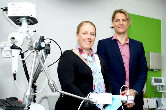 Dr Vanessa Murphy and Joerg Mattes stand side by side next to a piece of lab equipment