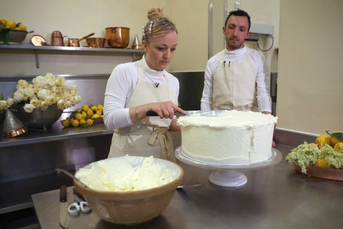 A baker finishes icing a tier of a cake, while another baker watches on.
