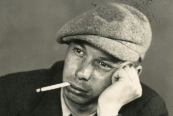 A young man rests his head on his hand with a cigarette in his mouth.