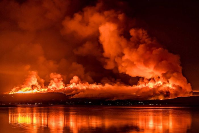 Bushfires burn on a hillside at night next to a body of water.