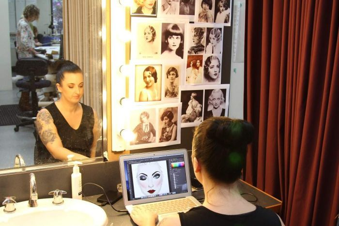 Woman sits before mirror looking at laptop, with photos pinned on wall