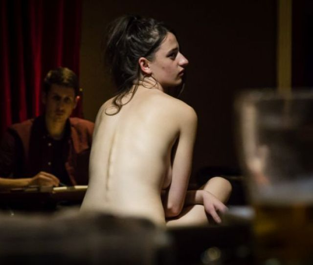 Nude Woman Posing In Life Drawing Group With Beer Glass In The Foreground