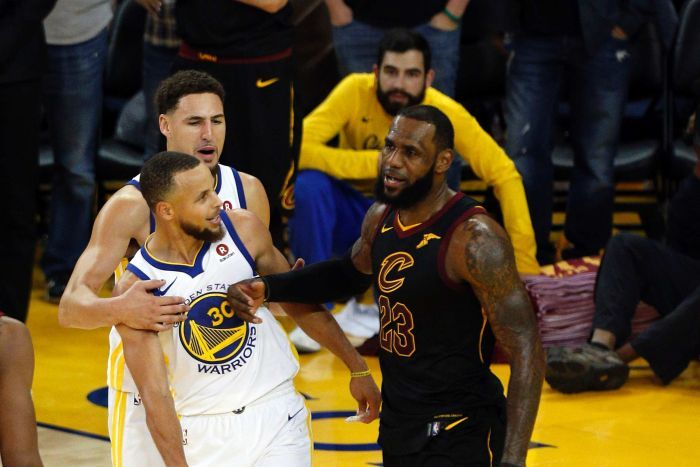 LeBron James pushes Steph Curry (left) with his forearm as Klay Thompson pulls Curry away.