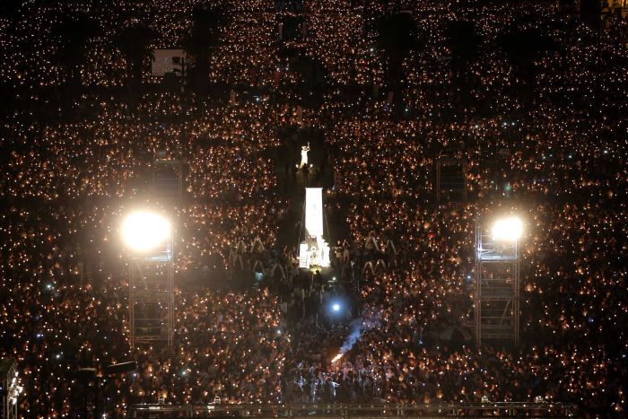 Tens of thousands of candles shine in the darkness.