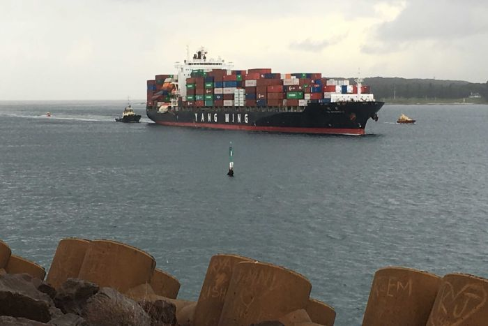 Tug boats escort a container ship into Port Botany.
