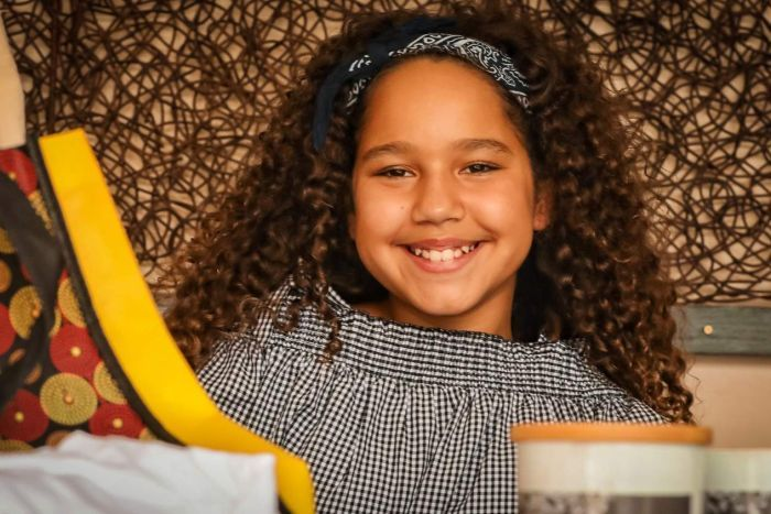 Young indigenous girl Téa Devow is smiling and showcasing traditional products.