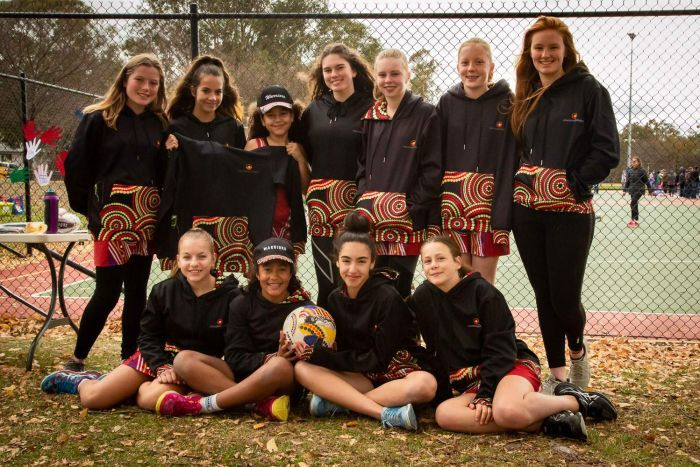 The Warriors netball team from Canberra are smiling together in a group.