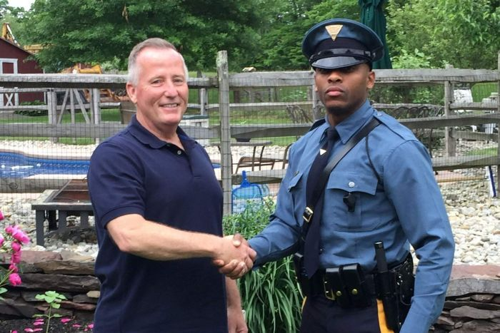 Trooper Michael Patterson in uniform shakes the hand of an older white male in plain clothes