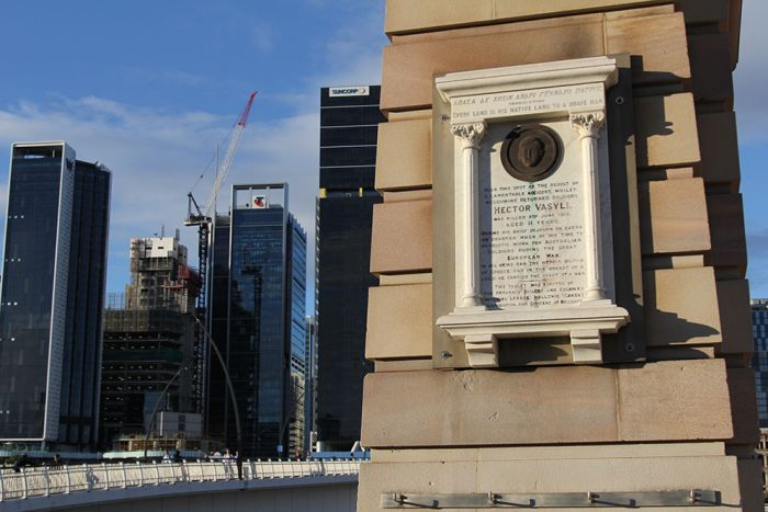 A stone memorial on an archway with Brisbane's Victoria Bridge in the background.