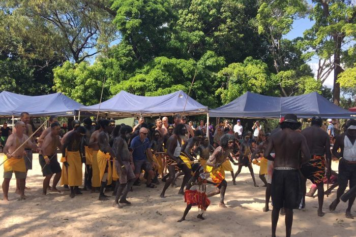 Paul Kelly participates in a traditional dance towards the memorial stone to Dr M Yunupingu.