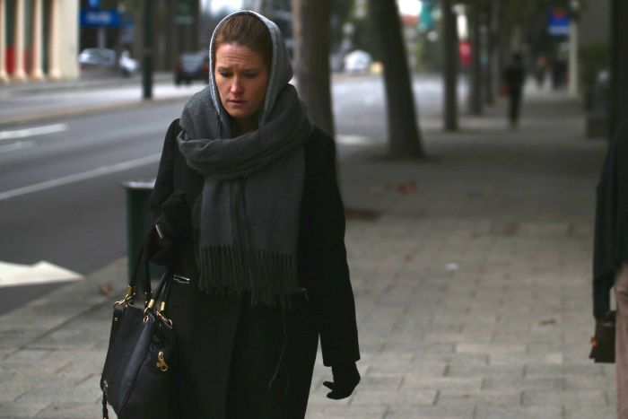 A woman wears a thick black jacket, gloves, and a scarf over her head in a cold morning on a city street.