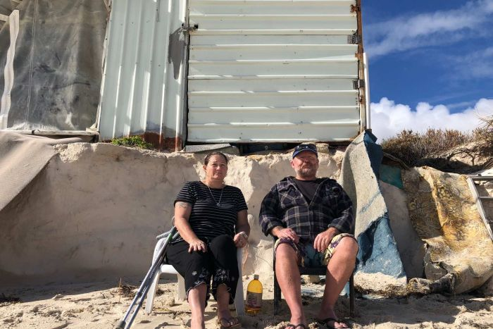 Kerry and Rob Howell sit in front of their crumbling shack.