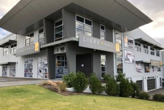 A wide shot of a grey Liebe and Haus store in Perth with shrubs in front.