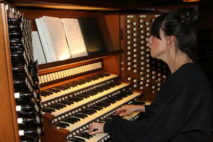 A woman looks at her notes while playing an organ.