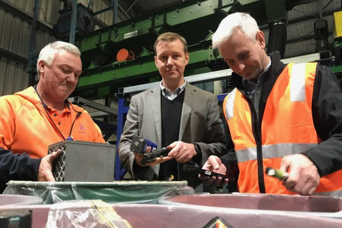 Three men, employees at Envirostream, take out batteries from metal drums ready for sorting.