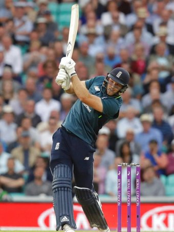 English cricket player David Willey swinging high with his cricket bat to hit a ball