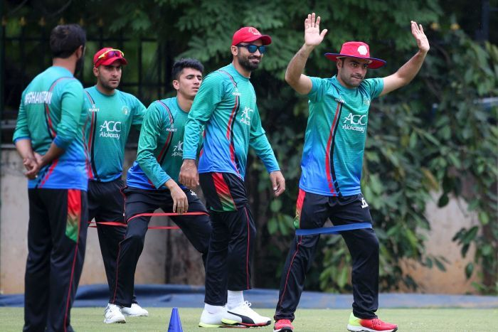 Afghan cricket team members in green team uniforms standing on a training pitch with one to the fore with arms raised.