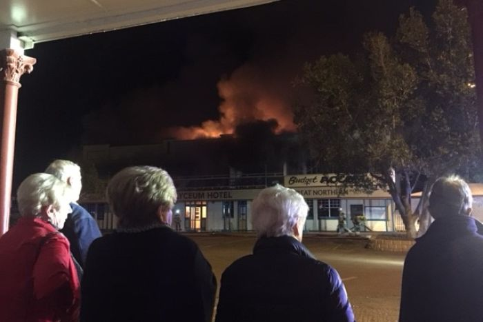 View of the back of five people watching flames and smoke pour out of the top of a building across the road from them