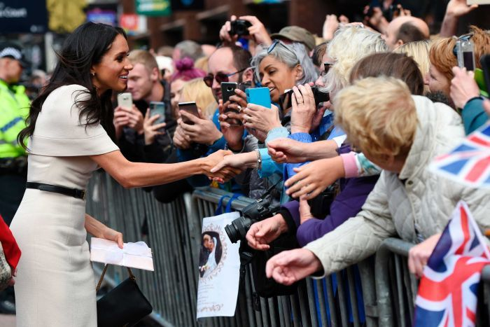 Meghan, Duchess of Sussex shakes hands with a fan as she walks along a street.