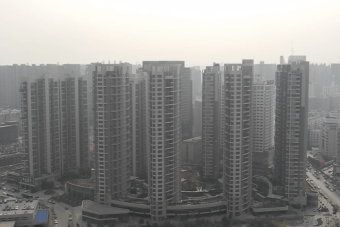 A cluster of apartment towers in a smoggy setting.