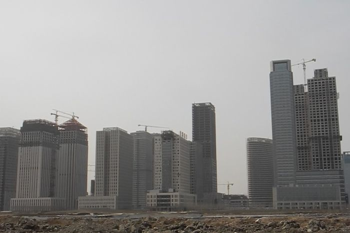 A row of tall apartment and office towers are under construction.
