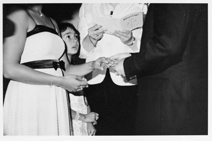 Black and white wedding photo of couple holding hands with young flower girl peering up at the groom in awe