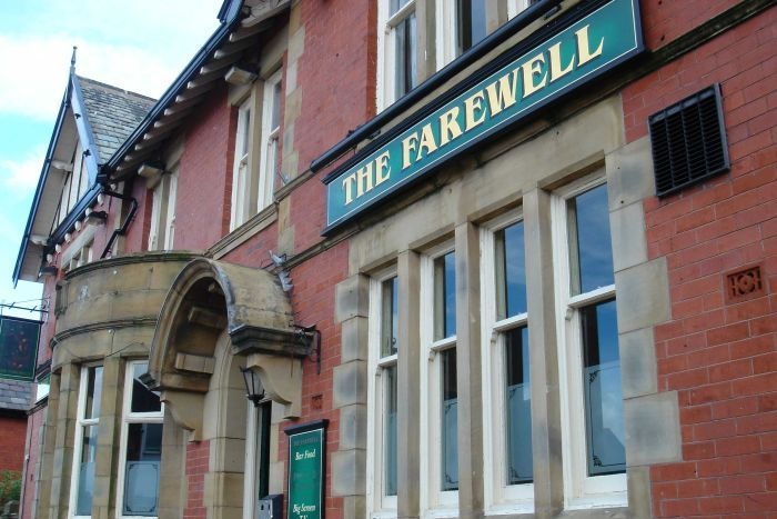 """The exterior of a red brick pub with a green sign saying """"the Farewell""""."""