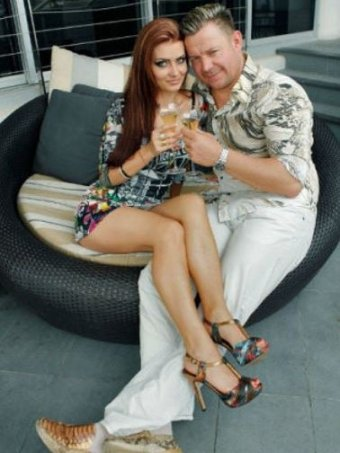 Vitali Roesch and his wife Marnya Kosukhina sitting on a outside couch with champagne in hand.