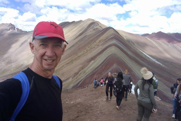 A selfie taken by a man in a red cap in front of a mountain with other tourists in the background.