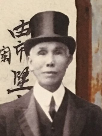 Kwong Sue Duk wears a suit and top hat and looks at the camera